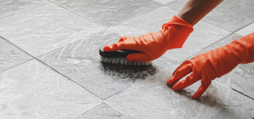 cleaning a tiled porcelain floor with a brush wearing safety gloves
