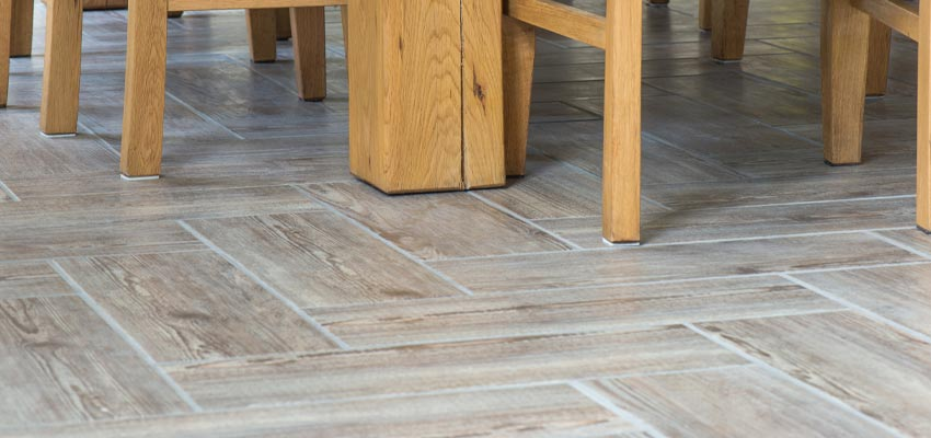 close up of porcelain tile floor with herringbone pattern and faded wood look